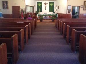 Mom prays inside the church of Nuestra Senora de Guadalupe in Lake Arthur.